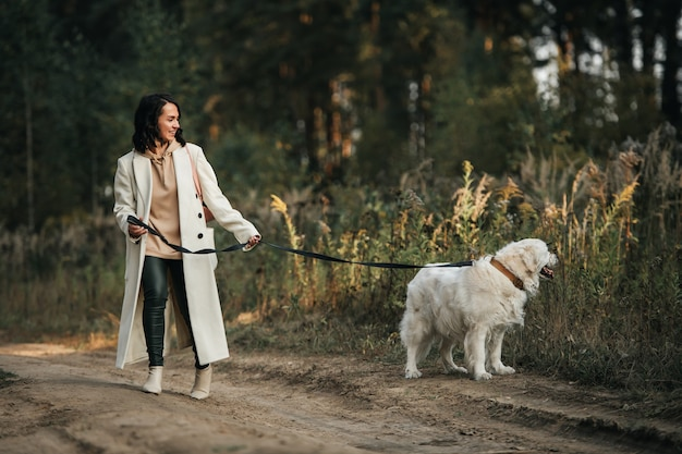 Meisje met witte gouden retrieverhond op het bospad