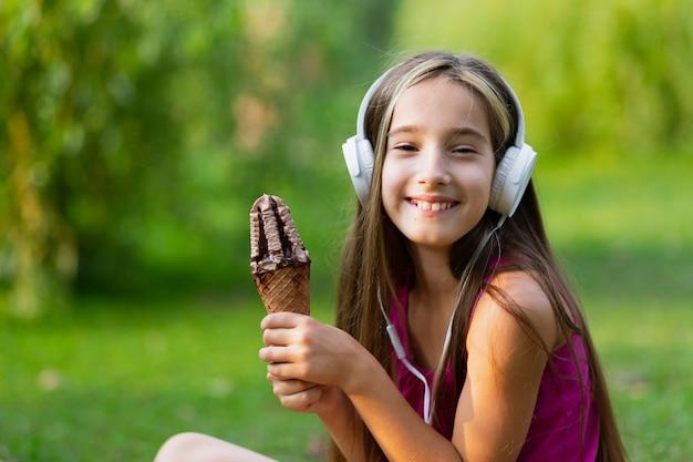 Meisje met witte hoofdtelefoons en chocoladeroomijs
