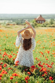 Meisje met witte jurk en strohoed loopt tussen rode papaverbloemen op de zonsondergang. jonge vrouw geniet van goede weer en plezier op het veld vol rode bloemen. lente en natuur concept
