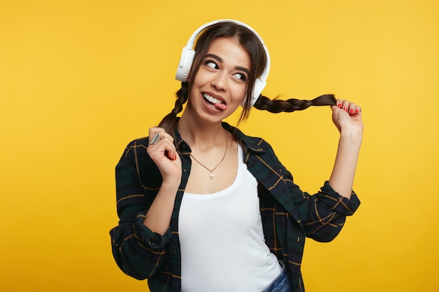 Meisje met witte koptelefoon speelt met haar paardenstaarten en steekt tong uit