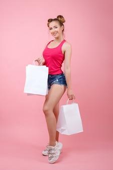 Meisje met witte zakken op een roze ruimte. boodschappen doen