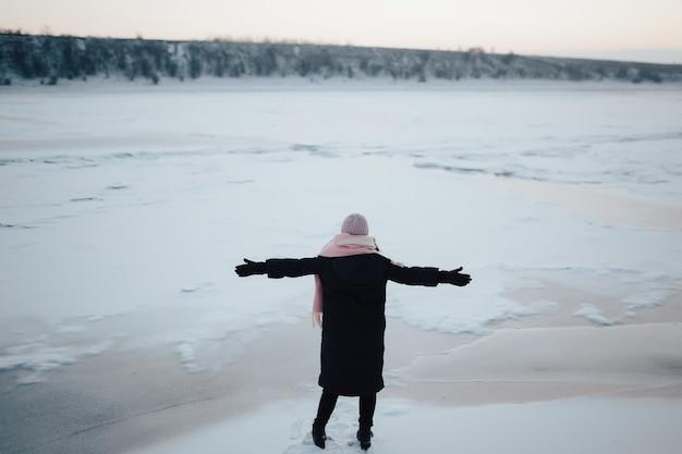 Meisje met wollen hoed, sjaal en zwarte jas genieten van prachtig landschap met bevroren rivier en heuvel.