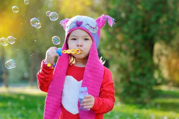 Meisje met zeepbellen in een gebreide met de hand gemaakte hoed