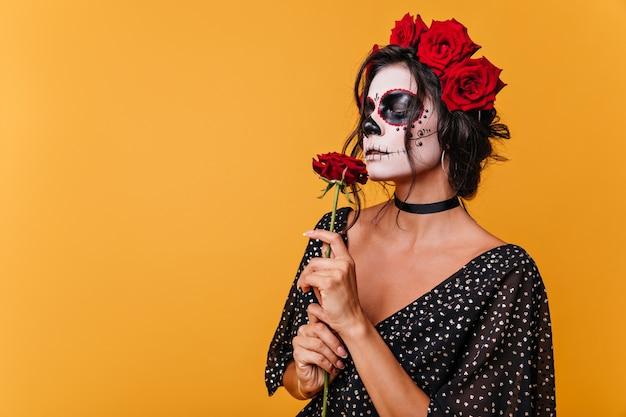 Meisje met zombiemasker voor halloween ruikt geurige roos. model in zwarte jurk op oranje muur