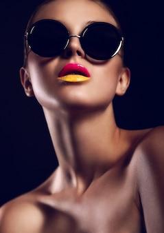 Meisje met zonnebril en duotoon lippen poseren