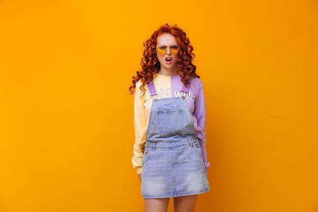 Meisje met zonnebril kijkt met ongenoegen en teleurstelling naar de voorkant tegen de oranje muur