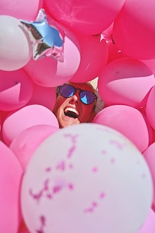 Meisje met zonnebril lacht tussen roze ballonnen