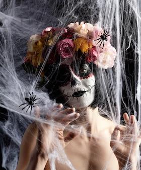 Meisje met zwart haar is gekleed in een krans van veelkleurige rozen en make-up wordt gemaakt op haar gezicht suikerschedel tot de dag van de doden
