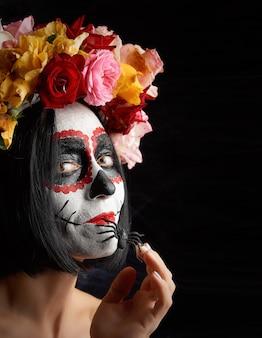 Meisje met zwart haar is gekleed in een krans van veelkleurige rozen en make-up wordt gemaakt op haar gezicht suikerschedel
