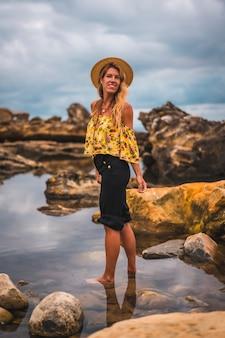 Meisje met zwarte korte broek en strohoed in een natuurlijk landschap aan zee bij zonsondergang