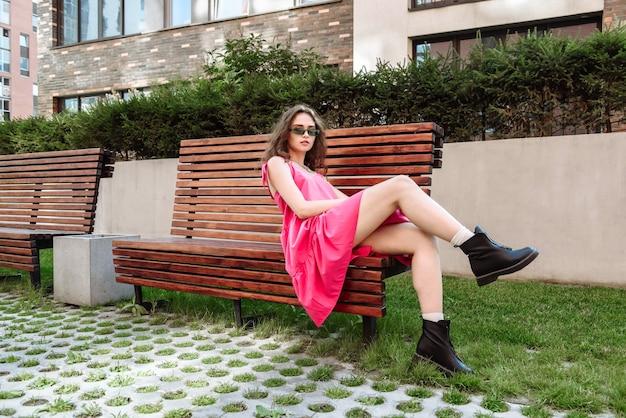 Meisje model poseren in modieuze kleding zittend op een bankje kledingcatalogus