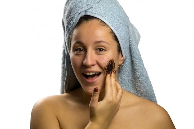Meisje na douche met een handdoek en verschillende gezichtsuitdrukkingen, gezicht met zelfgemaakte koffieroom