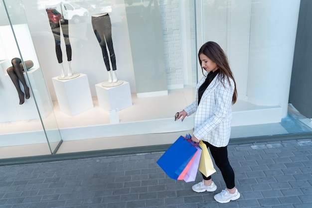 Meisje na succesvol winkelen houdt veelkleurige boodschappentassen vast. winkelverslaafd. showcase op achtergrond.
