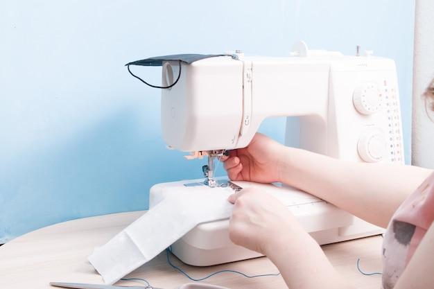 Meisje naait op een naaimachine een beschermend masker voor gezicht van grijze katoenweefsel, blauwe achtergrond