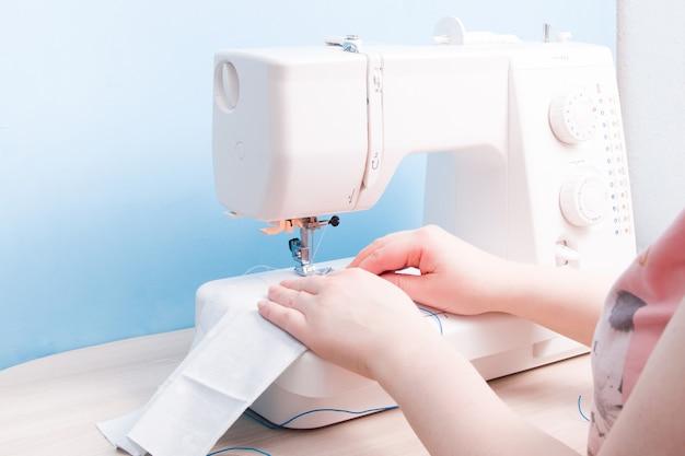Meisje naait op een naaimachine een beschermend masker voor gezicht van katoengrijze stof