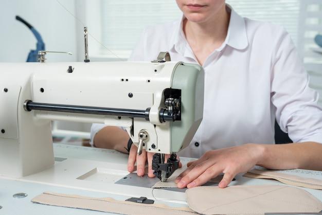 Meisje naait op een naaimachine krabbelt stof en leer om een product te maken