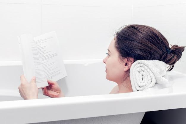 Meisje neemt een bad terwijl ze een boek leest in een witte badkamer