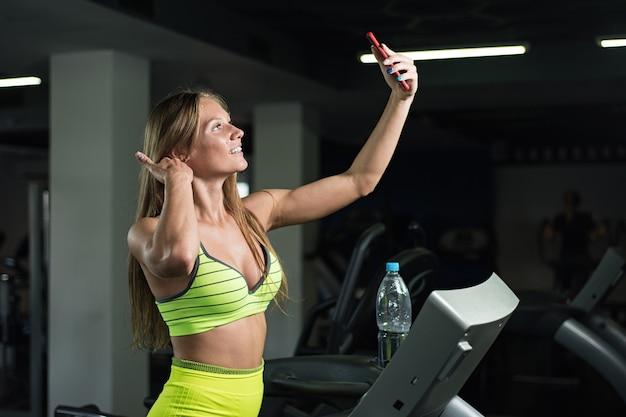 Meisje neemt een selfie in de sportschool, vrouw wordt gefotografeerd op de loopband