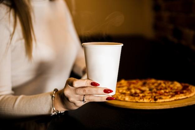 Meisje neemt een stuk pizza. fastfood, geen gezonde snack. eten bezorgen aan huis. rode peper, spek, tomaat, barbecuesaus. detailopname.