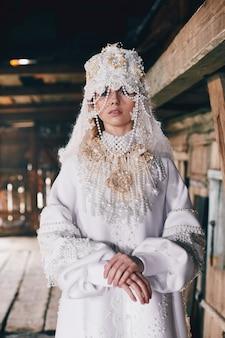 Meisje nieuwe etnische russische mode vogue creatieve kleren poseren in de buurt van oud huis