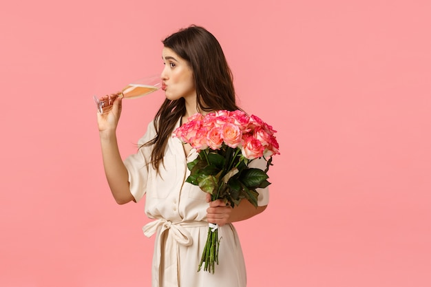 Meisje nipt champagne uit glas terwijl ze naar iemand gluurt, elegante jurk draagt, viert, feest heeft, rozen ontvangt, boeketbloemen, staande roze achtergrond geïntrigeerd en geamuseerd