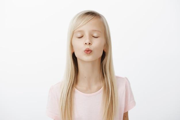Meisje oefenen in de buurt van spiegel hoe te kussen. portret van schattig modieus jong meisje met blond haar, lippen vouwen en ogen sluiten tijdens het wachten op een kus