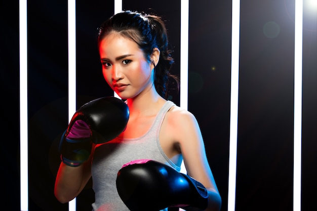 Meisje oefent zwaar in moderne neon boxing gym