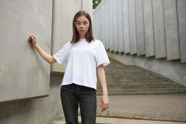 Meisje of vrouw met een wit leeg t-shirt met ruimte voor uw logo, mock-up of ontwerp in een casual stedelijke stijl urban