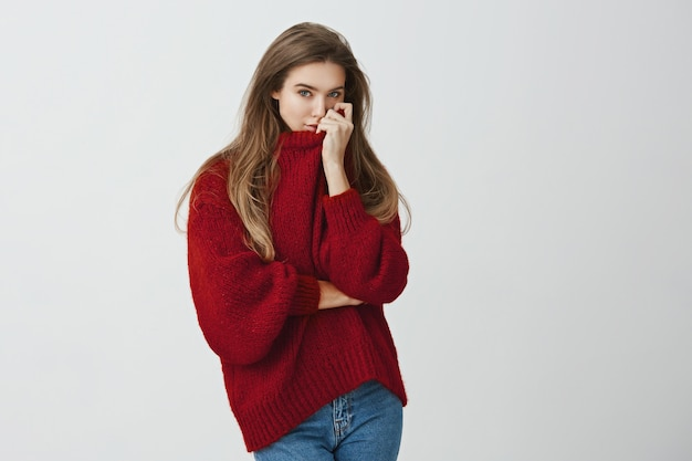 Meisje omhelsde vriendje en ruikt zijn parfum op haar trui. portret van sensueel knap europees model in trendy uitrusting die kraag op gezicht trekken terwijl status tegen grijze achtergrond.