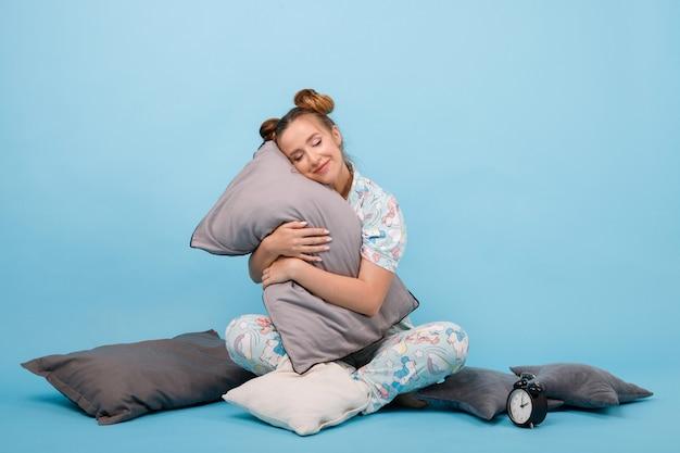 Meisje omhelst het kussen en wil niet wakker worden op een blauwe ruimte. goedemorgen