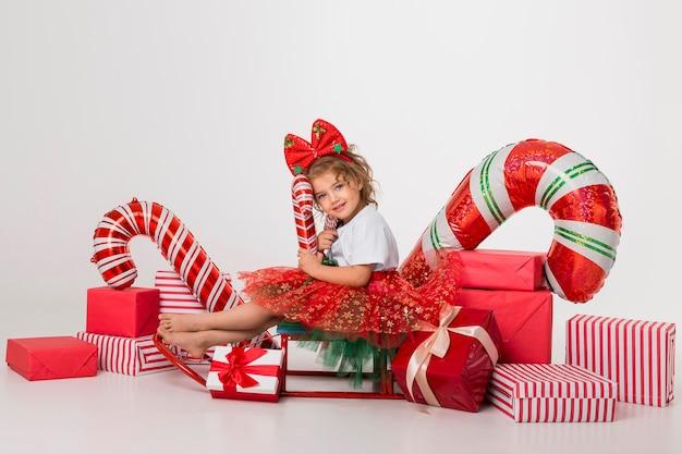 Meisje omringd door kerstelementen