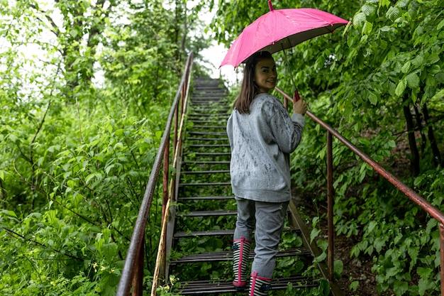 Meisje onder een paraplu op een wandeling in het lentebos in de regen