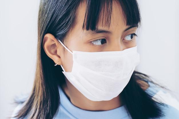 Meisje onder gezichtsmasker voor mond en neus. corona virus of covid-19-concept.
