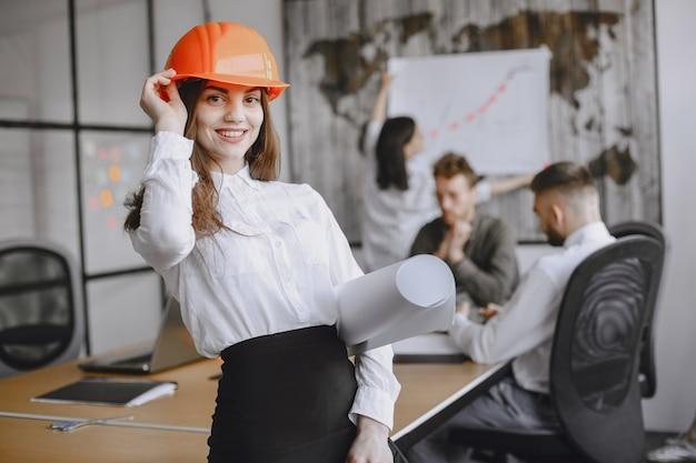 Meisje ondertekent de documenten. dame in een rode helm. managerl werkt op kantoor.