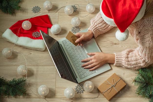 Meisje online winkelen voor kerstcadeautjes met kerstversiering