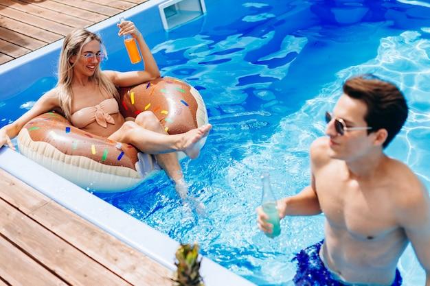 Meisje ontspant in het water, drijvend op een opblaasbare cirkel in het zwembad.