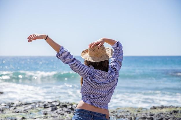 Meisje ontspant, raakt haar zomerhoed aan en zwaait met haar arm, vrijheid en vrije tijd concept.