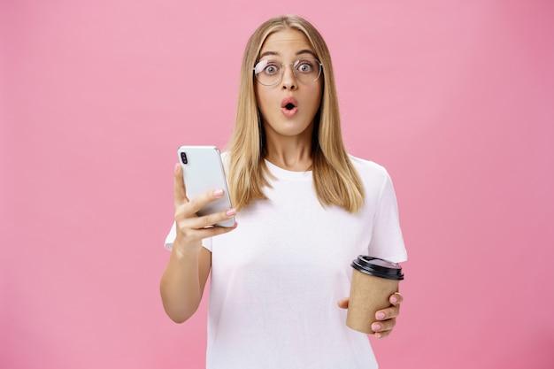 Meisje ontvangt geweldig bericht op smartphone terwijl ze koffie drinkt