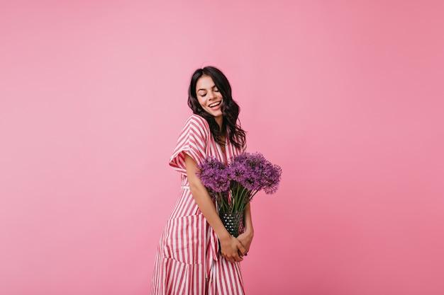 Meisje ontving bloemen als geschenk en verheugt zich. portret van brunette in romantische bui.