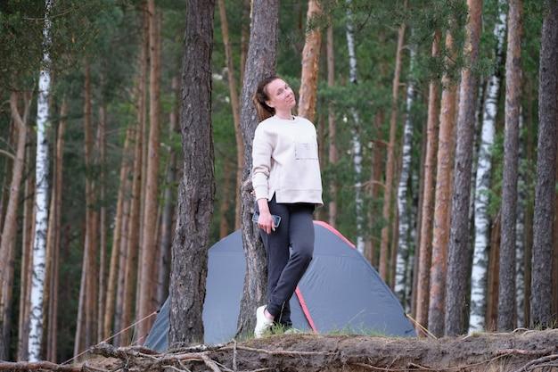 Meisje op de achtergrond van een tent in het bos. vakantieconcept.