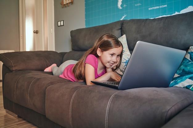 Meisje op de bank met behulp van de laptop