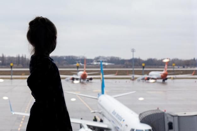 Meisje op de luchthaven buiten het raam kijkt naar het vliegtuig, wachtend op de vlucht