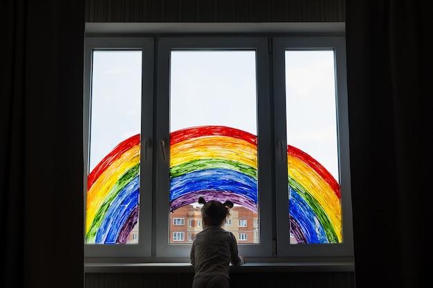 Meisje op de muur van het schilderen van regenboog op venster. kinderen vrije tijd thuis. positieve visuele ondersteuning tijdens de quarantaine van pandemic coronavirus covid-19 thuis.