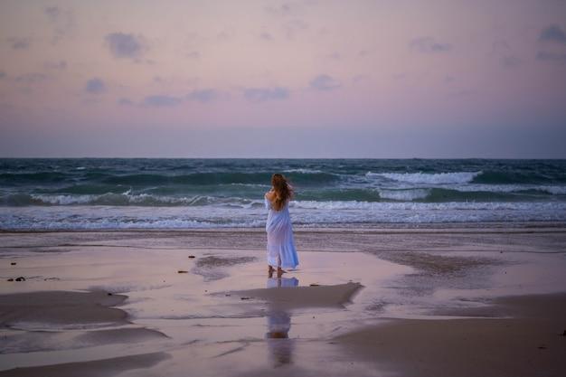 Meisje op de oceaan bij zonsondergang. concept: eenzaamheid, stilte, rust