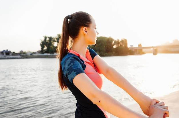 Meisje op de oever van de rivier opwarmen voor het joggen bij zonsondergang