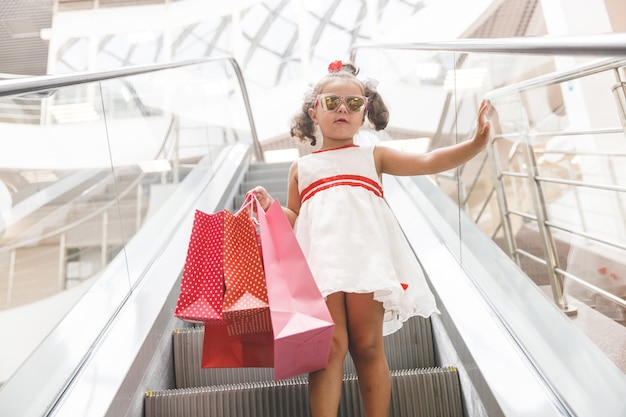 Meisje op de roltrap in het winkelcentrum met aankopen