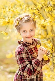 Meisje op een achtergrond van gele bloemen.