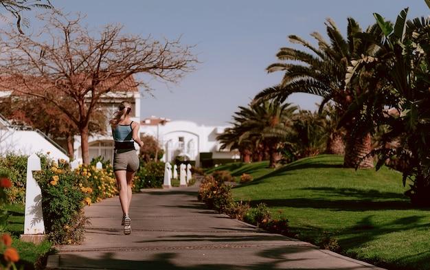 Meisje op een avond jog tussen palmbomen