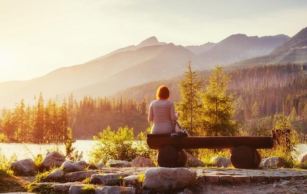 Meisje op een bankje bij zonsondergang