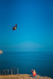 Meisje op een berghelling aan zee lanceert een vlieger op een zonnige dag